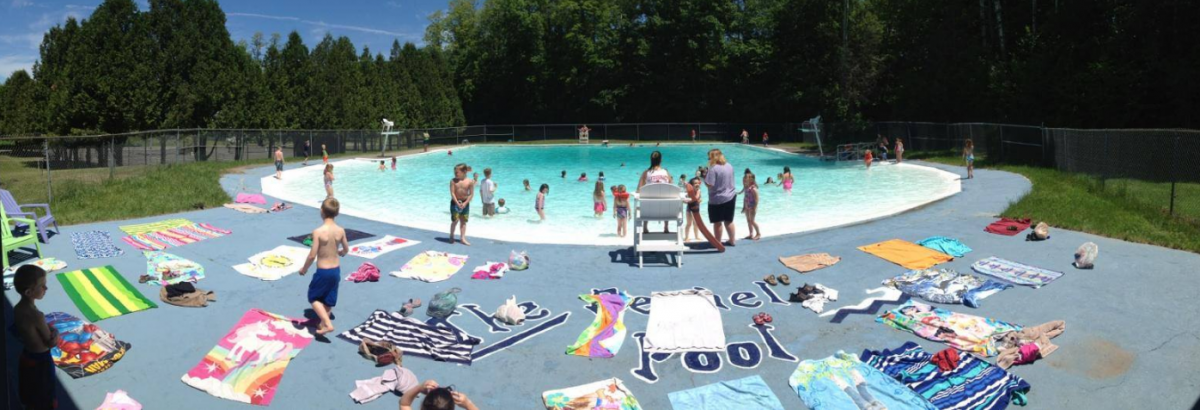Children and adults at an in-ground pool
