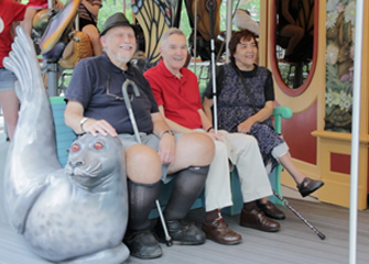 Still from the new Public Service Announcements. Three seniors riding a merry go round.